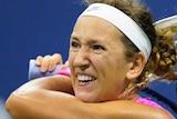 Victoria Azarenka grimaces as she holder her racquet in both hands behind her head