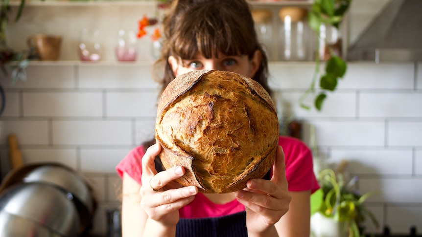 Woman holds a freshly baked sourdough loaf in her Adelaide kitchen, making sourdough at home.