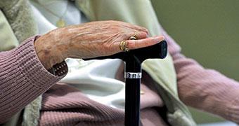 An elderly woman holds a walking stick.