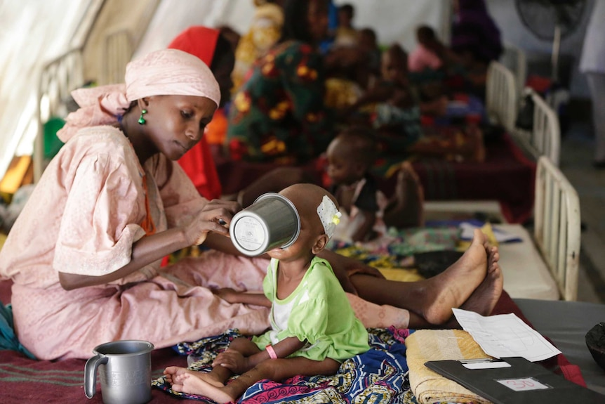 A mother feeds her malnourished child at a feeding centre.