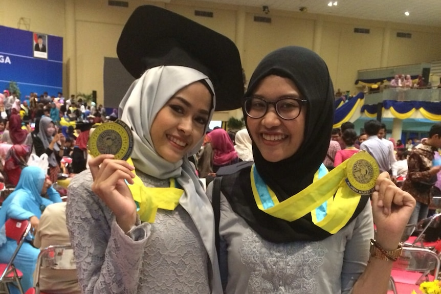 Two women wear formal attire and headscarves while holding medallions at a graduation ceremony