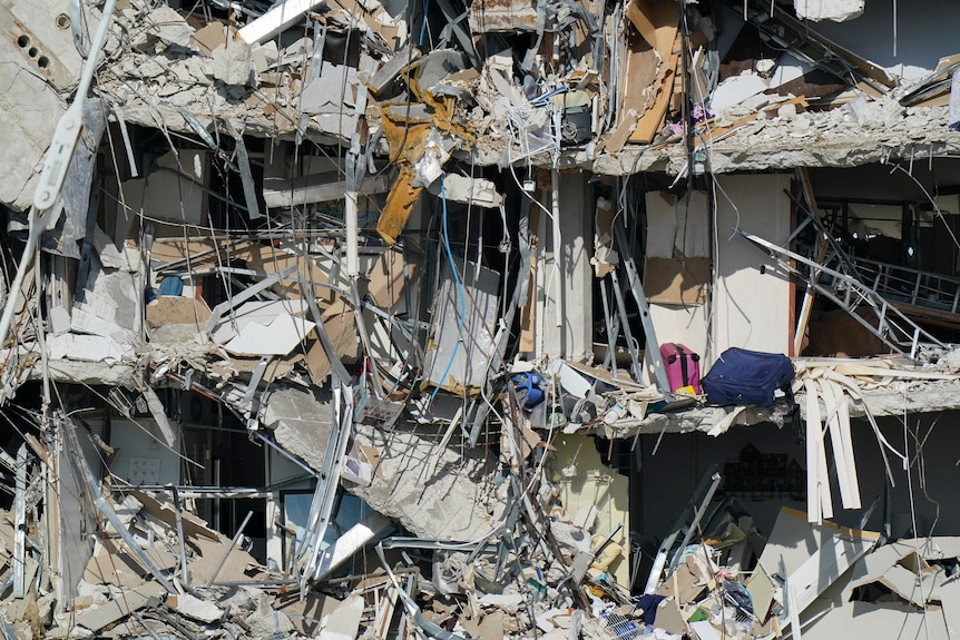 Personal belongings are seen amid debris dangling from the remains of apartments in Miami