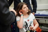 Young girl walks out of hospital wearing ID wrist bands and a T-shirt featuring a dog.