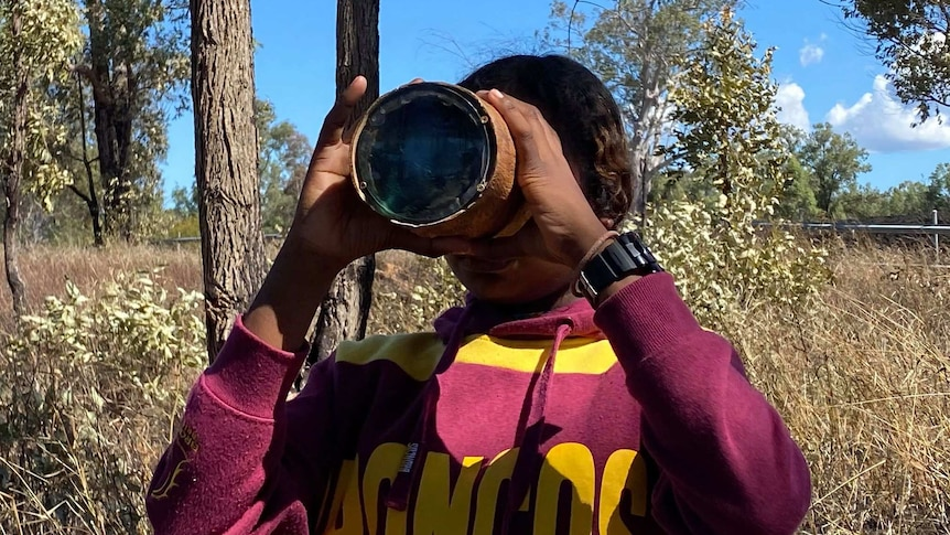 a student looks through a magnifying glass at the end of a hollowed log