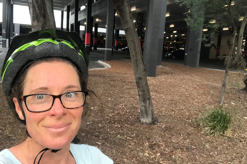 Nicola Thomas takes a selfie in front of a carpark while in her bicycle helmet.