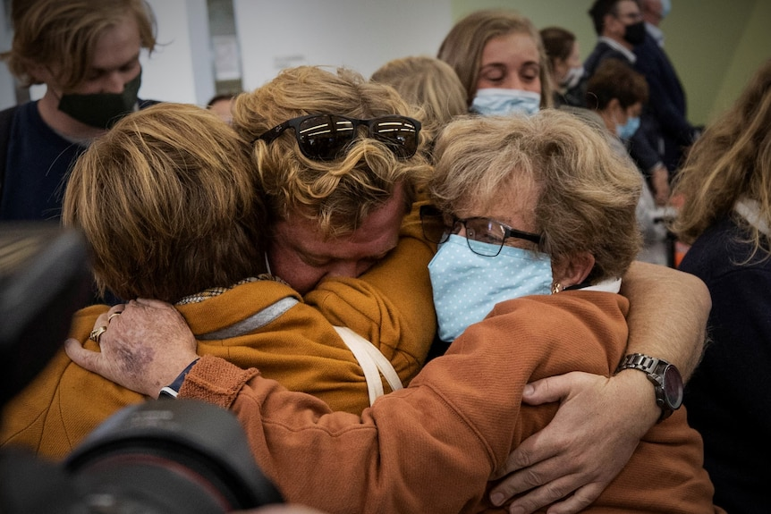Three people embracing at an airport.