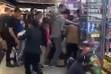 A scene showing people being knocked to the ground in a scramble to grab cans of baby formula from the shelves.