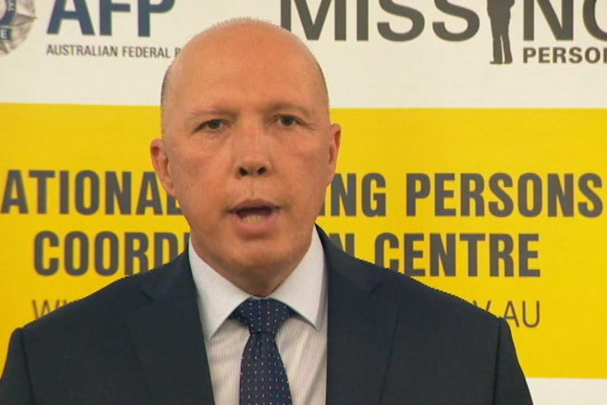 Peter Dutton speaks in front of a yellow and white background.