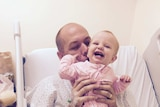 Adam Harvey with his daughter Isla in hospital after having a bullet removed from his neck