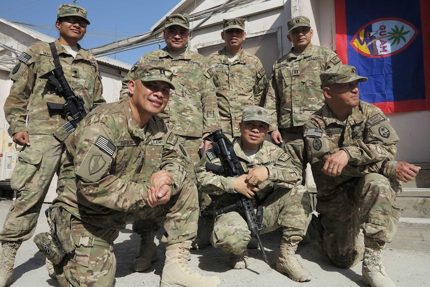 Seven soldiers of Micronesian appearance pose for a photo in US defence uniforms with a Guam flag hanging in the background.