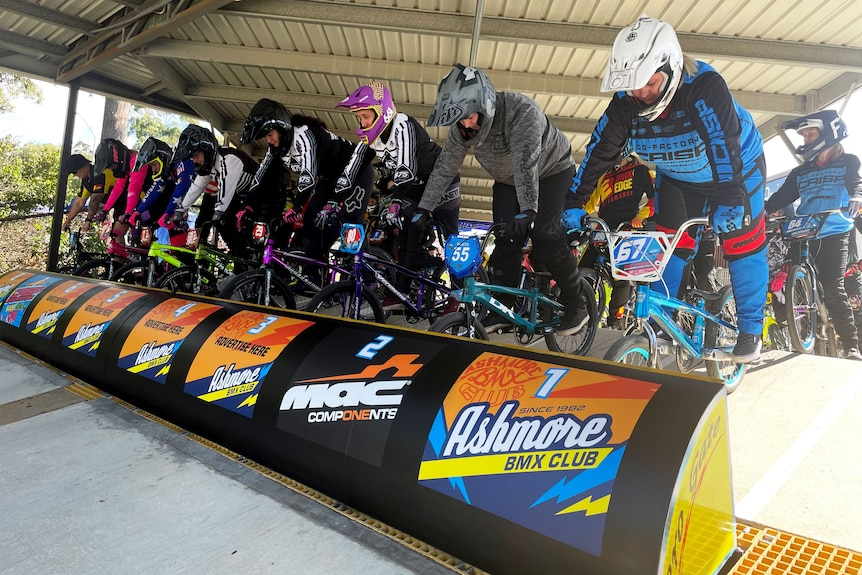 Female competitors line up at the gate at a BMX bike race meet on Queensland's Gold Coast.
