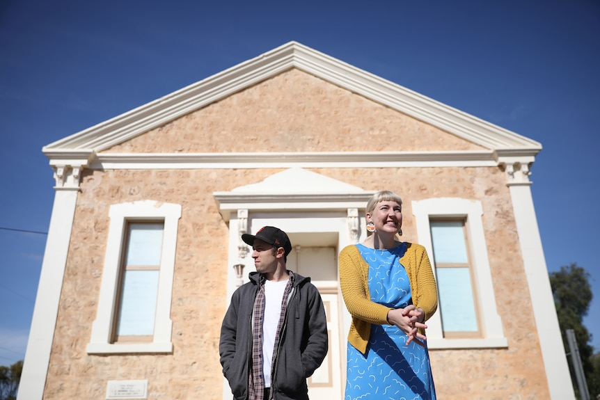 A man and a woman stand in front of an old hall looking in opposite directions.