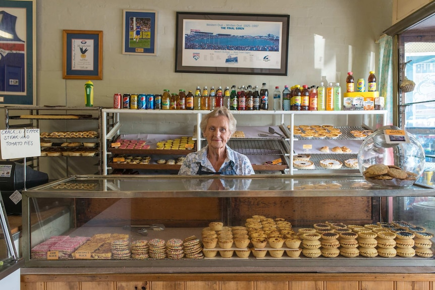 A woman stands behind the counter of a bakery.