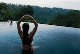 Woman sitting in a pool making a love heart symbol with her hands.