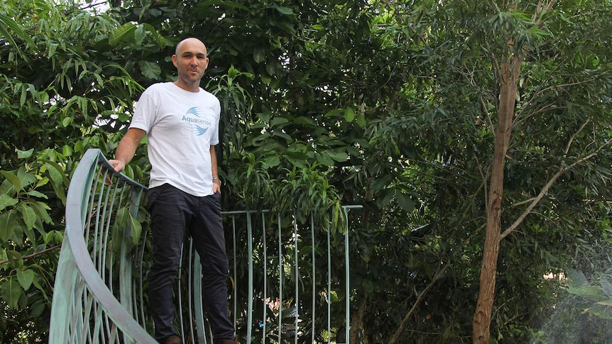 Entrepreneur Michael Bruvel standing next to his above-ground pool in an Aquasense t-shirt.