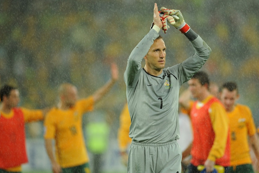 Mark Schwarzer lifts his arms in the air wearing a grey goalkeeper's outfit with several Australian soccer players behind.