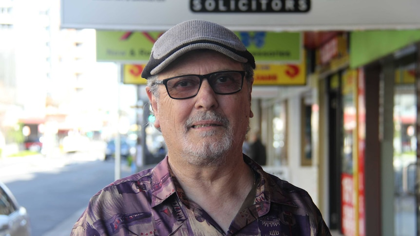 Older man with hat and glasses on standing in street.