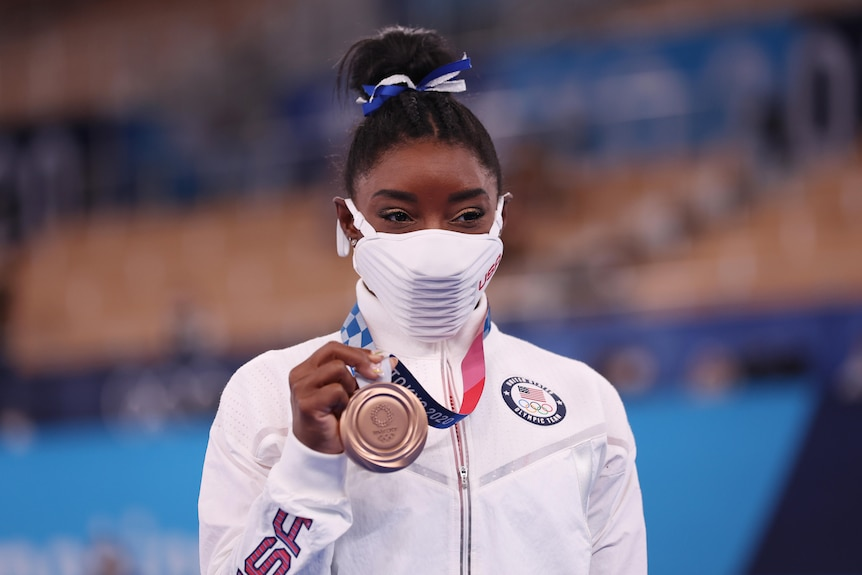 Simone Biles wears a mask but appears to be smiling as she holds up her bronze medal.
