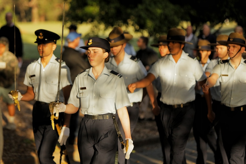 A female Australian Airforce cadet marches in a parade with others holding a sword.