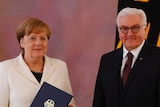 Angela Merkel holds her certificate of appointment and stands next to President Frank-Walter Steinmeier.