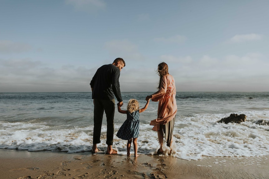 A man and a woman each hold a child's arms while facing the ocean on a beach.