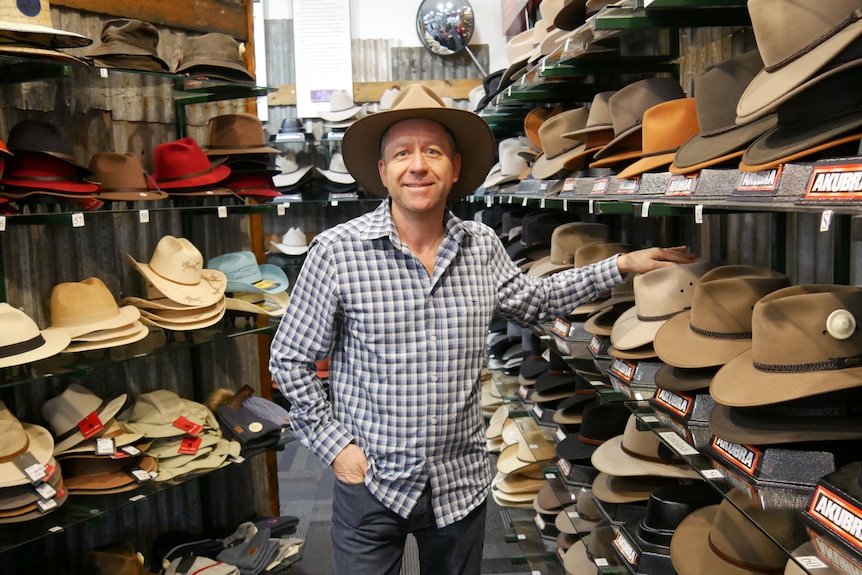 man wearing checked shirt and akubra hat standing in between two shop walls of akubra hats