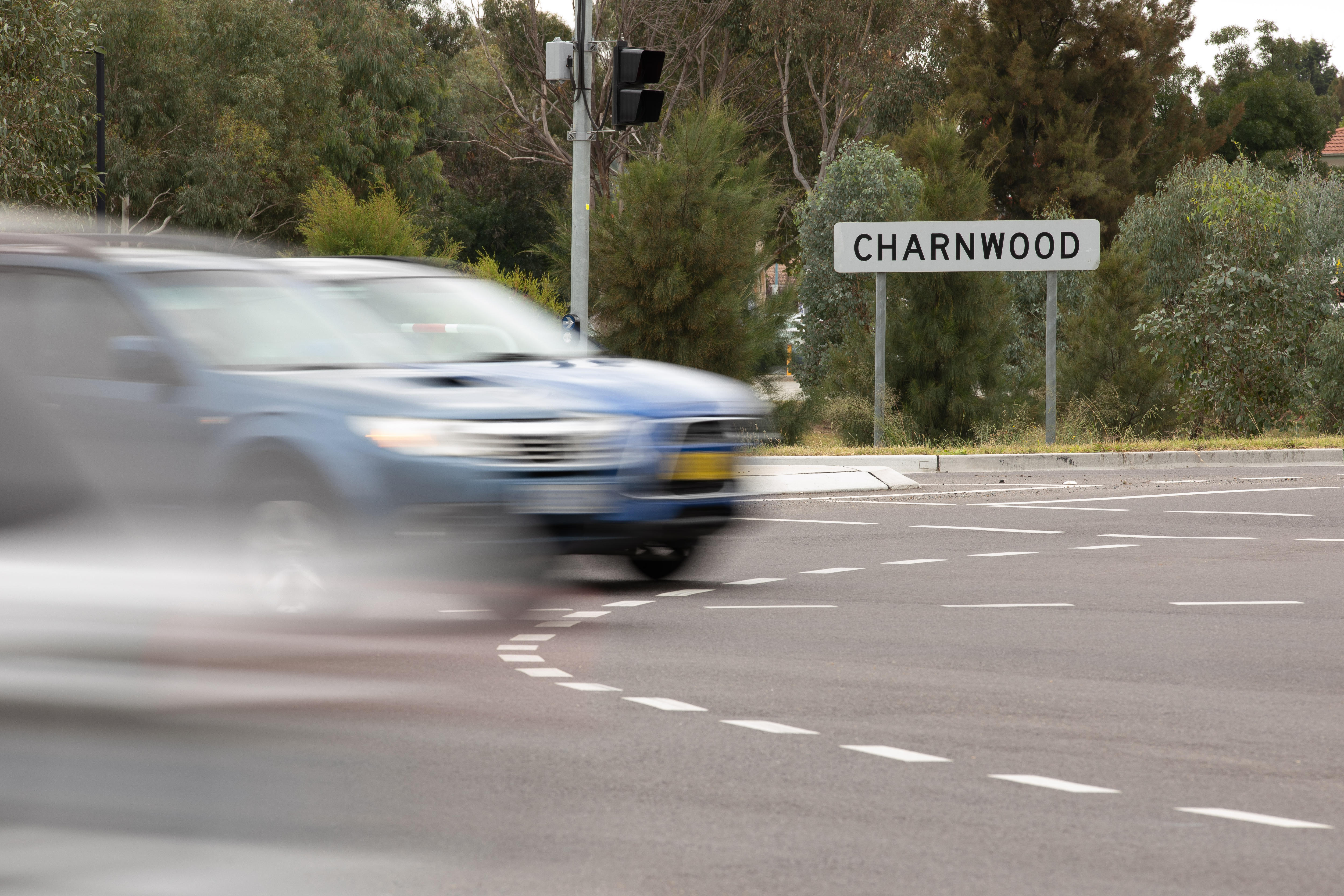 A grey car drives past a Charnwood sign.