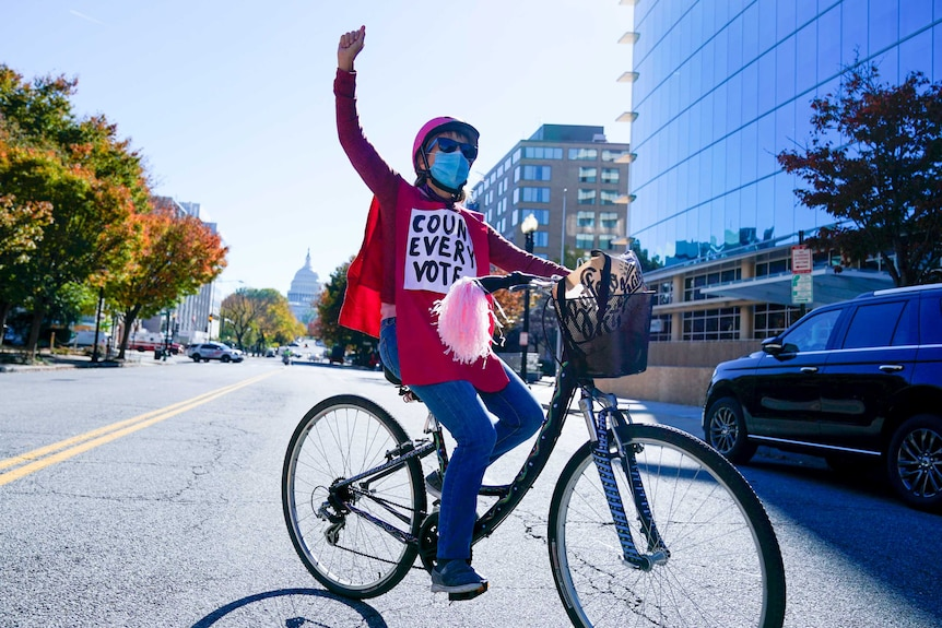 A woman on a bike with her fist in the air and a sign on her chest reading 'count every vote'