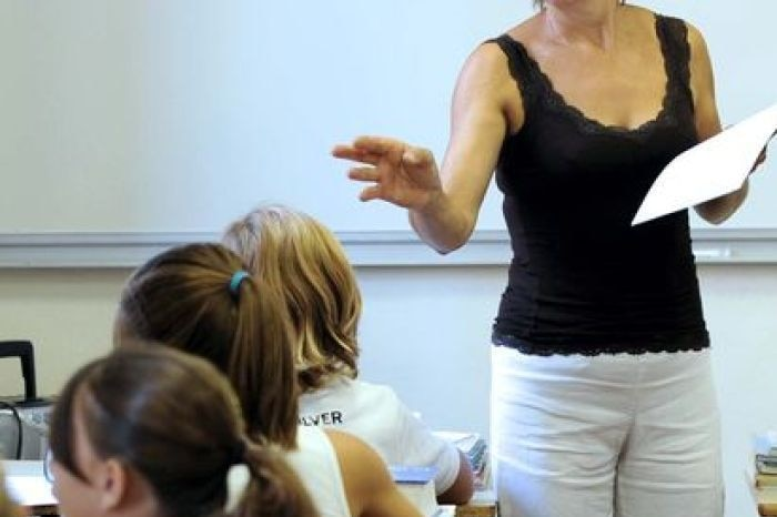 A teacher gives instructions to her pupils in a classroom