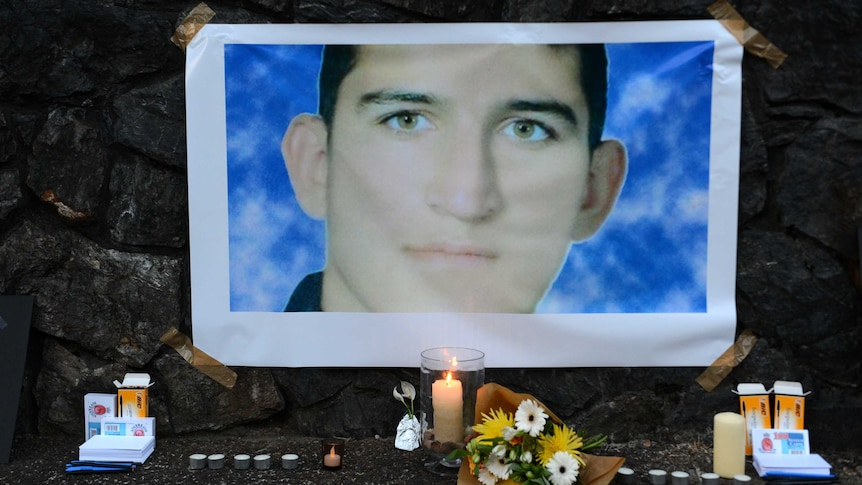 A photograph of Reza Barati sits above candles and flowers in a small shrine display.
