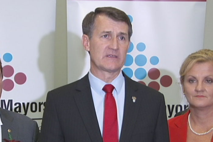 A man with dark hair, wearing a dark suit and a bright tie, addresses the media.