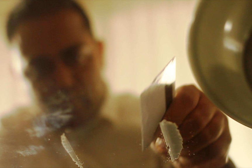 A man prepares lines of cocaine on a table.