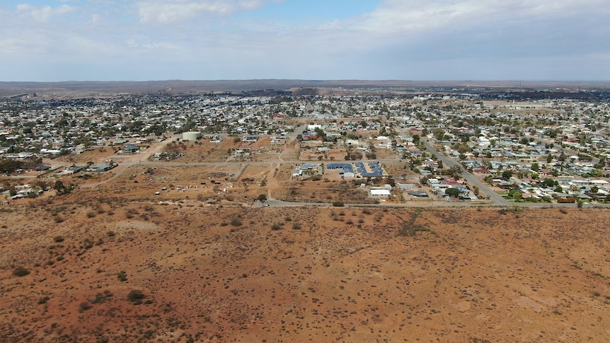 Aerial image of a remote town surrounded by red desert sand