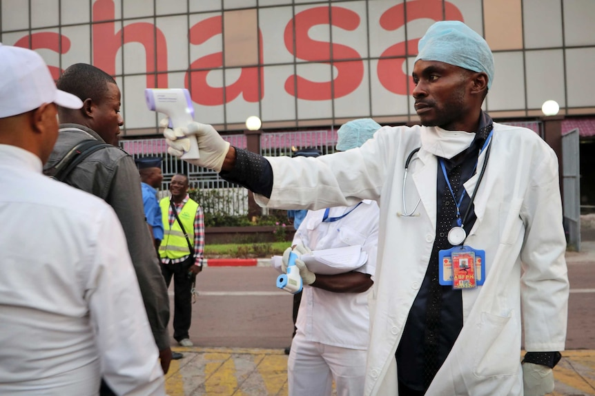 A health worker checks people's temperatures as they disembark a plane