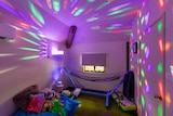 a dark room with bright lights, a hammock and toys.
