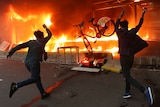 Two protesters hurl a bicycle to a burning metro station with black smoke taking up most of the photo.