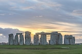 Sun rises through clouds over the stone monument known as Stonehenge.
