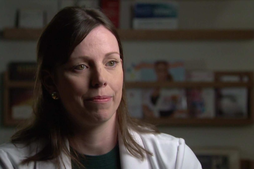 Dr Rowena Mobbs wearing a white blazer and a green top, with brown hair and green eyes.