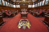 The upper house of WA parliament from inside, showing red carpet and red chairs around a central desk.
