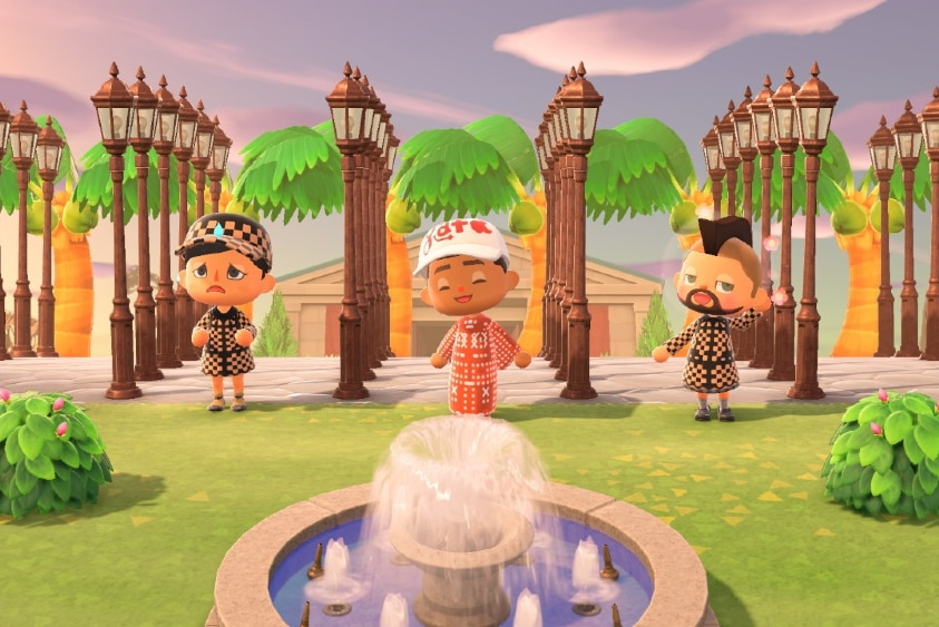 Three 3D characters in patterned outfits stand near fountain and in front of six rows of five cast iron street lamps and museum.