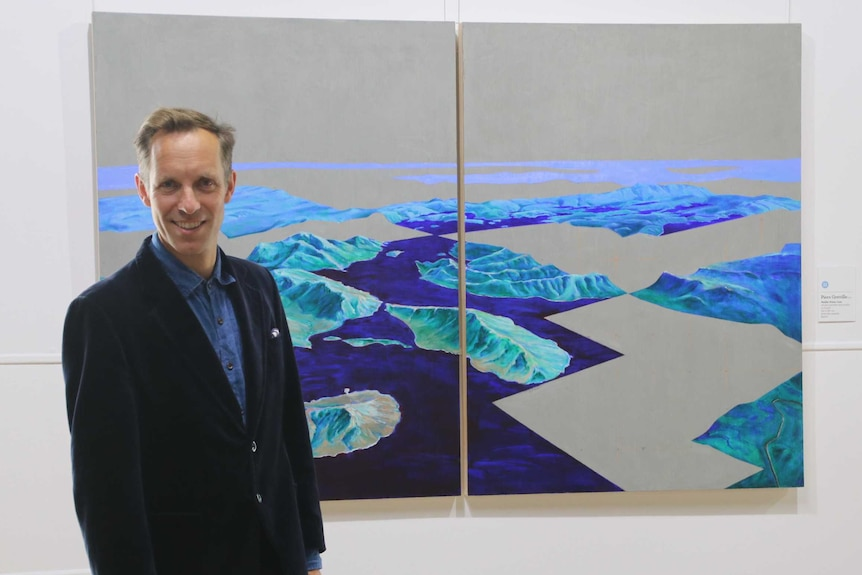 Glover Prize winner Piers Greville standing next to his winning artwork Pedder Prime Cuts, March 2019.