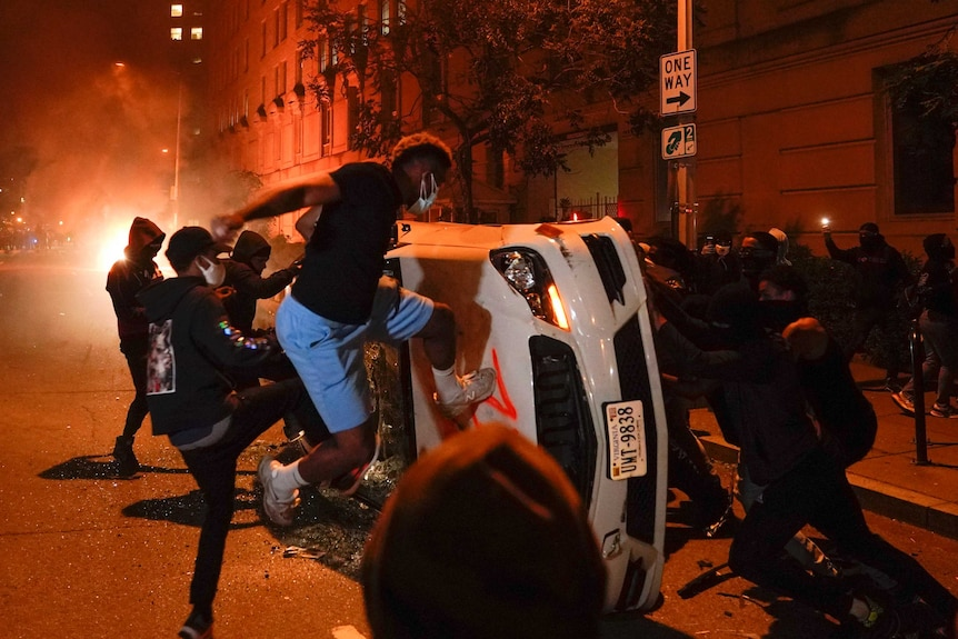 A group of young men wearing face masks kick a car that has been pushed onto its side while fires burn in the background.
