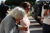 A woman walks from court with her mother after giving evidence at a trial.