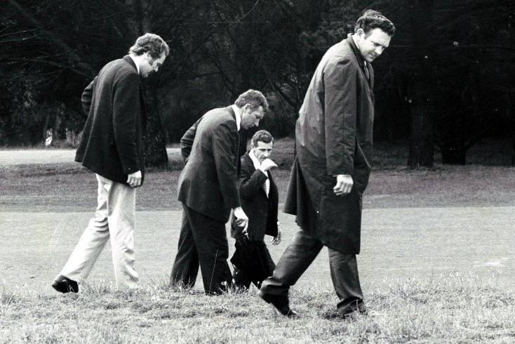 A black and white photo of four men with their heads down looking at the grass