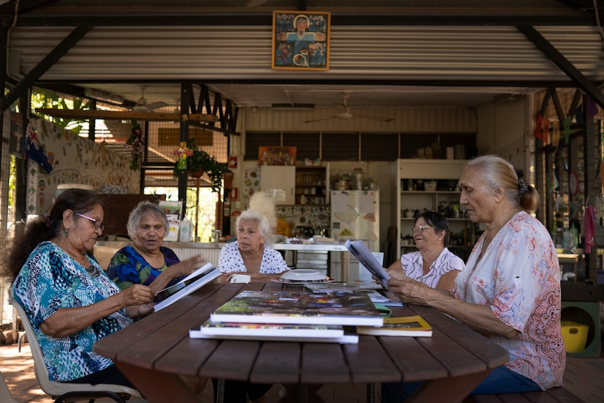Five women sit around a table.