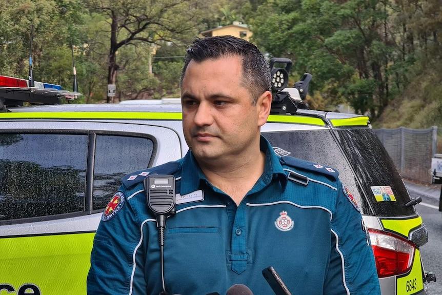 Queensland Ambulance Serviceacting operations supervisor Jay Nevinstalks to media in front of police car.