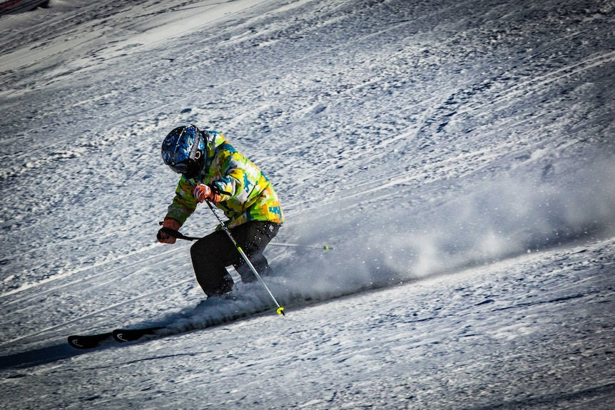 A person in a helmet and colourful jacket skis down a slope.