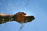 Water splashes onto a hand with sunlight in the background.