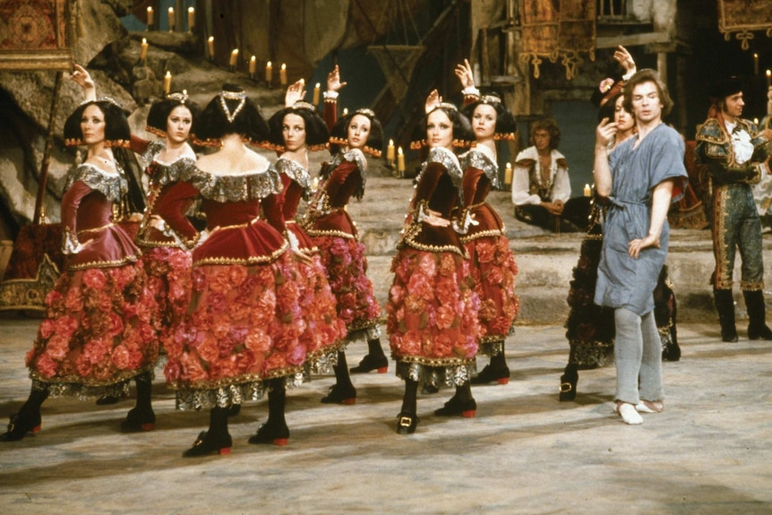 One male ballet dancer with eight female dancers in red costumes.