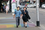 A man and a woman wearing face masks walk on a Melbourne street.